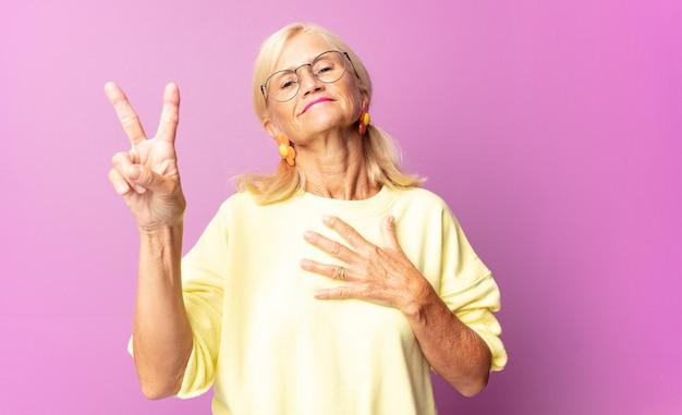 Kobieta w średnim wieku wyglądająca na szczęśliwą, pewną siebie i godną zaufania, uśmiechnięta i pokazująca znak zwycięstwa, z pozytywnym nastawieniem
