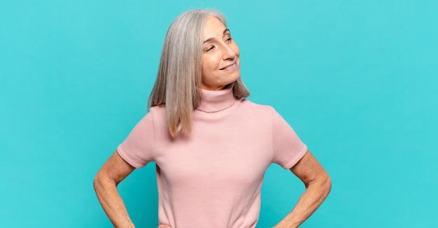 Kobieta w średnim wieku wyglądająca na szczęśliwą, pogodną i pewną siebie, uśmiechającą się dumnie i patrzącą na bok z obiema rękami na biodrach