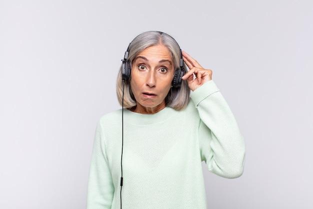 Kobieta w średnim wieku wyglądająca na szczęśliwą, zdumioną i zaskoczoną, uśmiechnięta i dostrzegająca niesamowite i niewiarygodnie dobre wieści. koncepcja muzyki