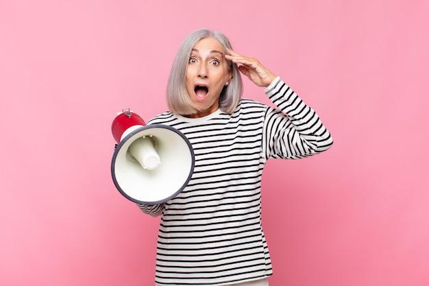 Kobieta w średnim wieku wyglądająca na szczęśliwą, zdziwioną i zaskoczoną, uśmiechnięta i realizująca przez megafon niesamowitą i niesamowicie dobrą wiadomość