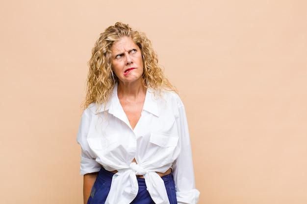 Kobieta w średnim wieku wyglądająca na zaskoczoną i zdezorientowaną, zastanawiająca się lub próbująca rozwiązać problem lub myśląca