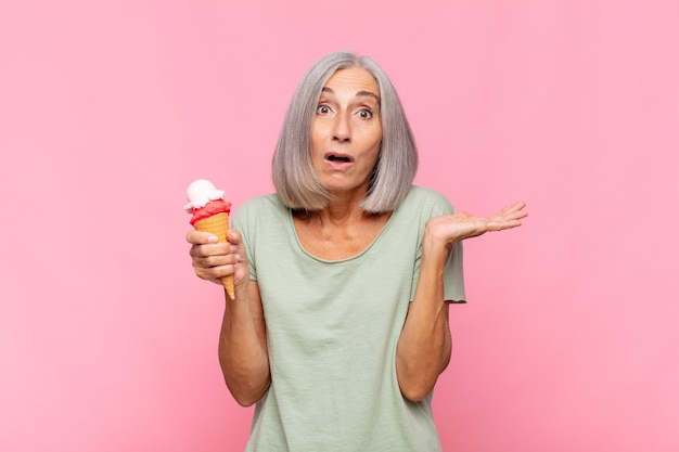 Kobieta w średnim wieku wyglądająca na zaskoczoną i zszokowaną, z opuszczoną szczęką trzymająca przedmiot z otwartą dłonią z boku z lodami