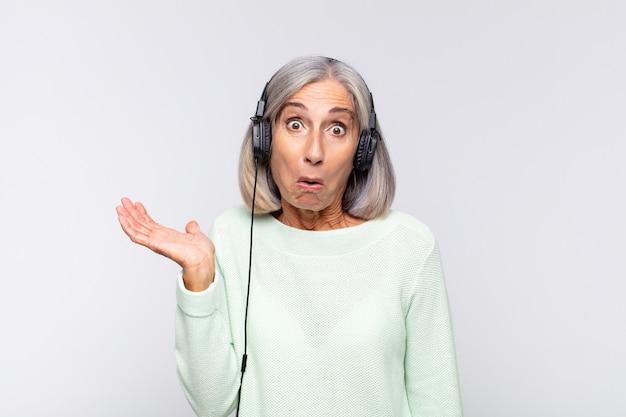 Kobieta w średnim wieku wyglądająca na zaskoczoną i zszokowaną, z opuszczoną szczęką, trzymająca przedmiot z otwartą ręką z boku. koncepcja muzyki