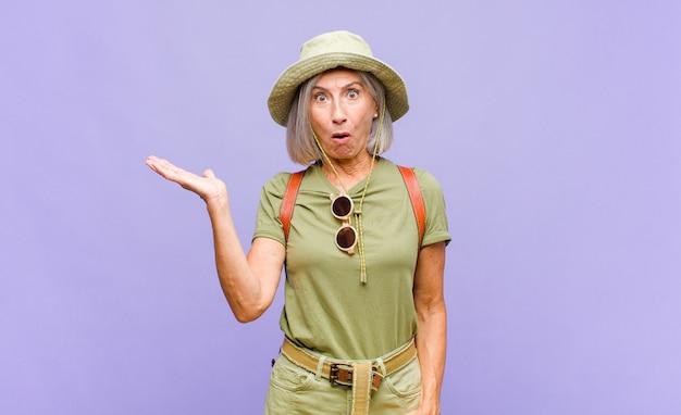 Kobieta w średnim wieku wyglądająca na zaskoczoną i zszokowaną, z opuszczoną szczęką trzymająca przedmiot z otwartą ręką z boku