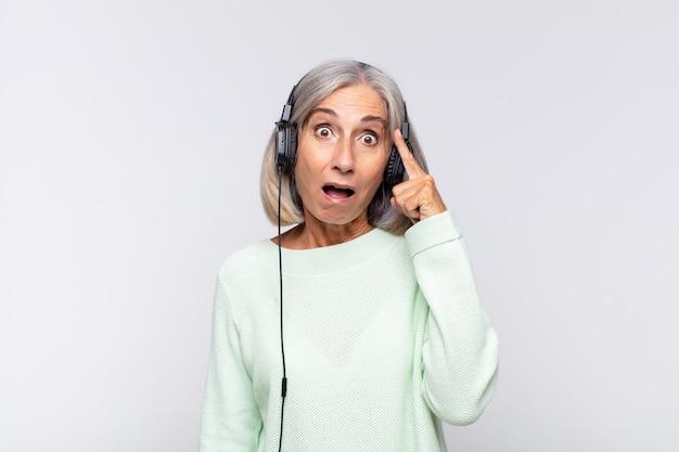 Kobieta w średnim wieku wyglądająca na zaskoczoną, z otwartymi ustami, zszokowana, uświadamiająca sobie nową myśl, pomysł lub koncepcję. koncepcja muzyki
