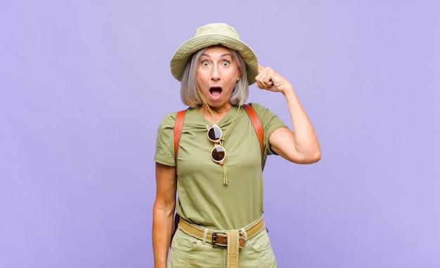 Kobieta w średnim wieku wyglądająca na zaskoczoną, z otwartymi ustami, zszokowana, uświadamiająca sobie nową myśl, pomysł lub koncepcję