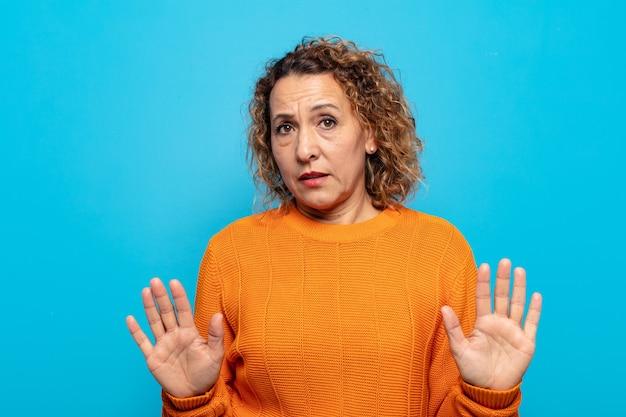Kobieta w średnim wieku wyglądająca na zdenerwowaną, niespokojną i zaniepokojoną, mówiącą, że to nie moja wina lub nie zrobiłam tego