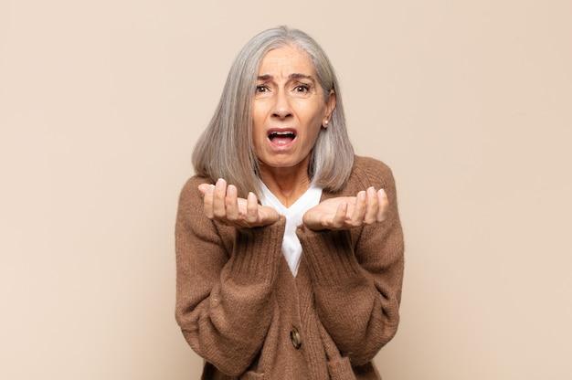 Kobieta w średnim wieku wyglądająca na zdesperowaną i sfrustrowaną, zestresowaną, nieszczęśliwą i zirytowaną, krzyczącą i krzyczącą