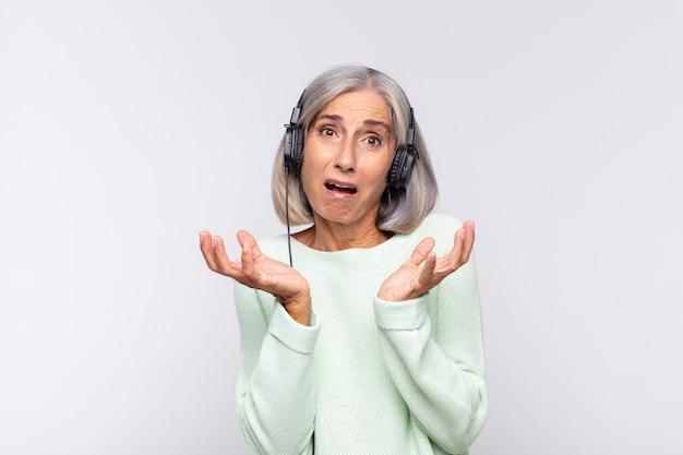 Kobieta w średnim wieku wyglądająca na zdesperowaną i sfrustrowaną, zestresowaną, nieszczęśliwą i zirytowaną, krzyczącą i wrzeszczącą. koncepcja muzyki