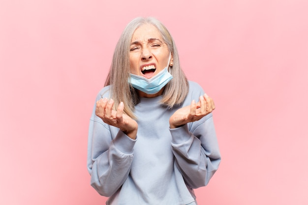 Kobieta w średnim wieku wyglądająca na zdesperowaną i sfrustrowaną, zestresowaną, nieszczęśliwą i zirytowaną, krzyczącą i wrzeszczącą