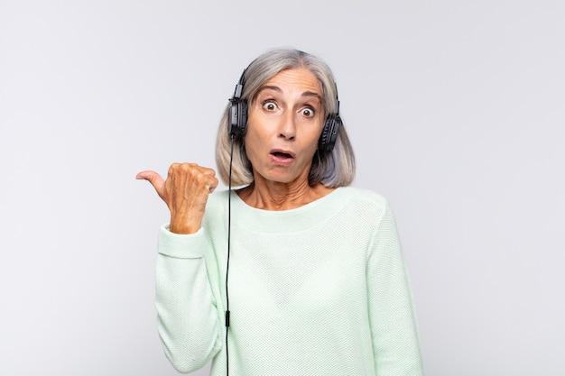Kobieta w średnim wieku wyglądająca na zdumioną z niedowierzaniem i wskazująca