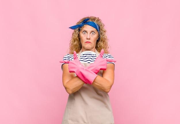 Kobieta w średnim wieku wyglądająca na zdziwioną i zdezorientowaną, niepewną siebie i wskazującą w przeciwnych kierunkach z wątpliwościami
