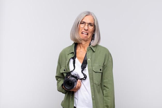 Kobieta w średnim wieku wyglądająca na zdziwioną i zdezorientowaną, przygryzając wargę nerwowym gestem, nie znając odpowiedzi na problem. koncepcja fotografa