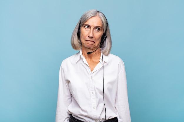 Kobieta w średnim wieku wyglądająca na zdziwioną i zdezorientowaną, przygryzając wargę nerwowym gestem, nie znając odpowiedzi na problem. koncepcja telemarketera