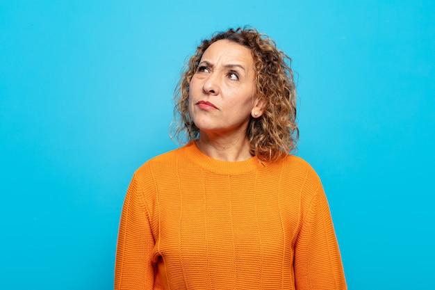 Kobieta w średnim wieku wyglądająca na zdziwioną i zdezorientowaną, zastanawiającą się lub próbującą rozwiązać problem lub myślącą