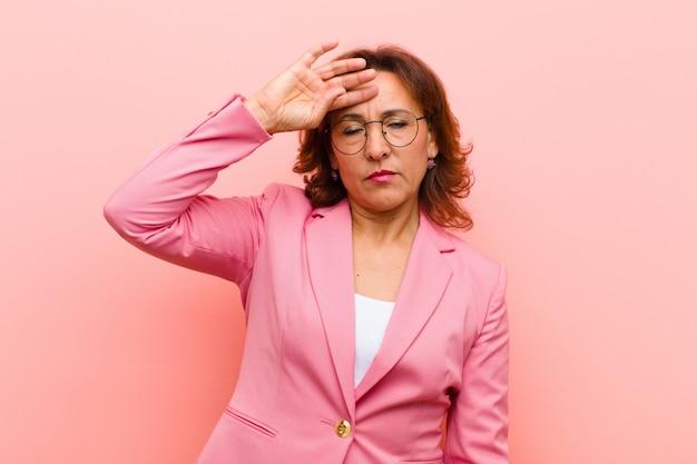 Kobieta w średnim wieku, wyglądająca na zestresowaną, zmęczoną i sfrustrowaną, wysuszającą pot z czoła, czuje się beznadziejnie i wyczerpana