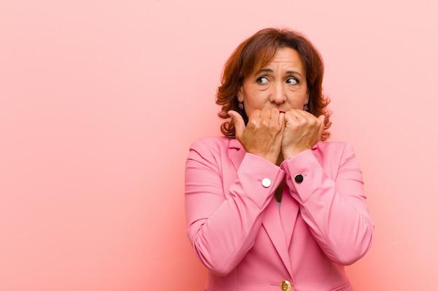 Kobieta w średnim wieku, wyglądająca na zmartwioną, niespokojną, zestresowaną i przestraszoną, obgryzająca paznokcie i szukająca bocznej przestrzeni kopii