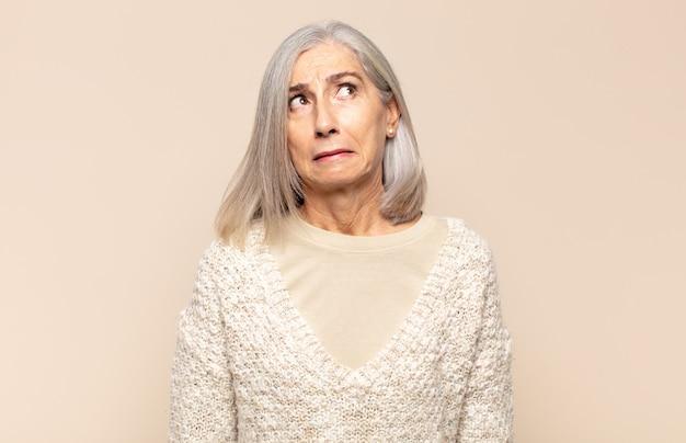 Kobieta w średnim wieku wyglądająca na zmartwioną, zestresowaną, niespokojną i przestraszoną, panikującą i zaciskającą zęby