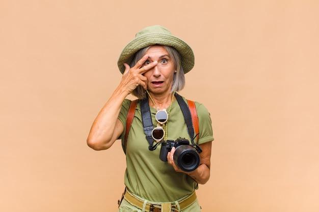 Kobieta w średnim wieku wyglądająca na zszokowaną, przestraszoną lub przerażoną, zakrywającą twarz dłonią i zaglądającą między palce
