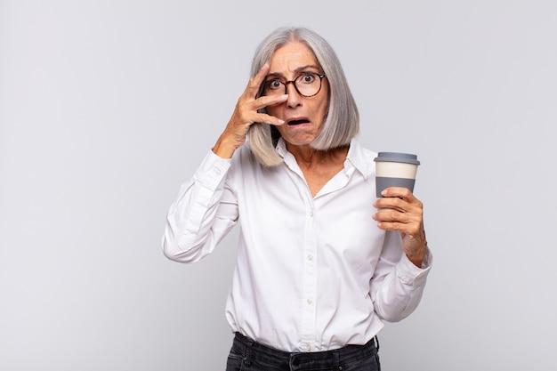 Kobieta w średnim wieku wyglądająca na zszokowaną, przestraszoną lub przerażoną, zakrywająca twarz dłonią i zerkająca między palcami koncepcja kawy