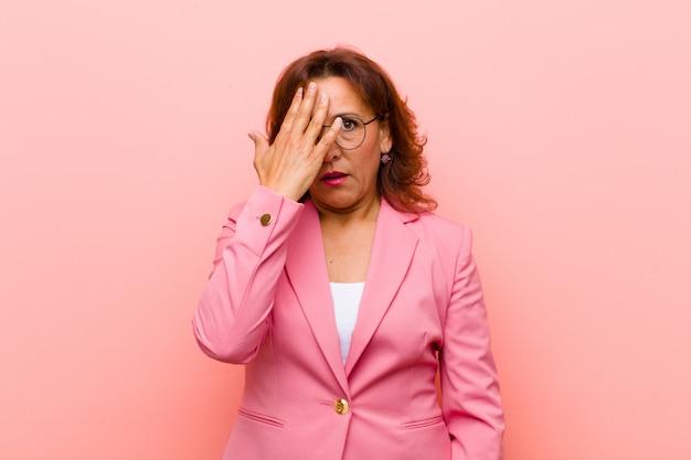 Kobieta w średnim wieku wyglądająca na zszokowaną, przestraszoną lub przerażoną, zakrywającą twarz dłonią i zerkającą między palcami na różową ścianę