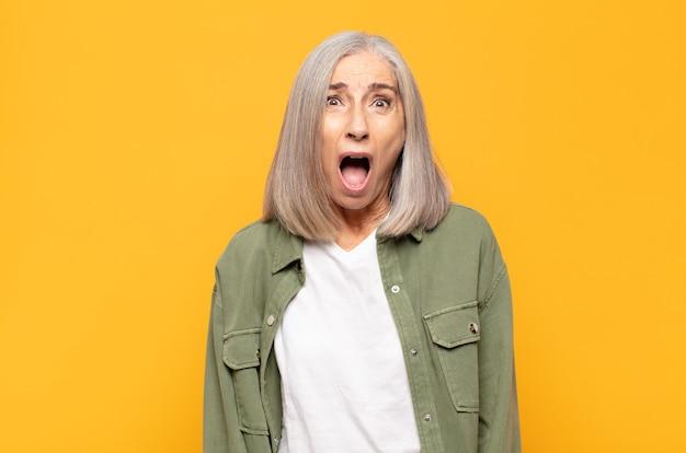 Kobieta w średnim wieku wyglądająca na zszokowaną, złą, zirytowaną lub rozczarowaną, z otwartymi ustami i wściekłymi