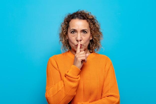Kobieta w średnim wieku, wyglądająca poważnie i krzywo, z palcem przyciśniętym do ust, domagająca się ciszy lub spokoju, dochowania tajemnicy