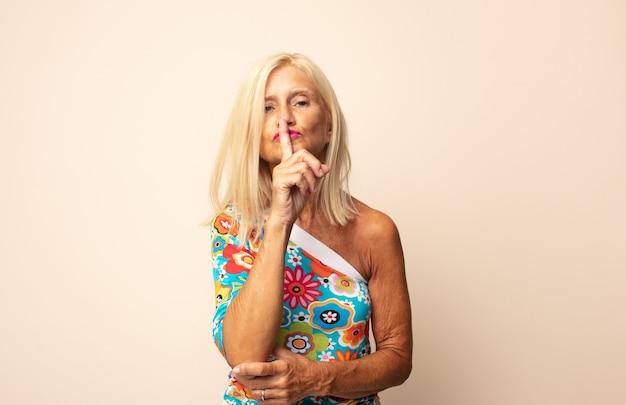 Kobieta w średnim wieku, wyglądająca poważnie i krzywo, z palcem przyciśniętym do ust, domagająca się ciszy lub spokoju, zachowywania tajemnicy
