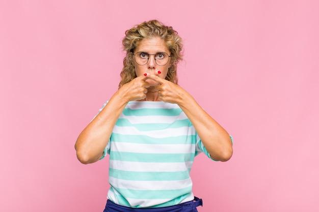 Kobieta w średnim wieku, wyglądająca poważnie i niezadowolona, z dwoma palcami skrzyżowanymi z przodu z odmową, prosząca o ciszę