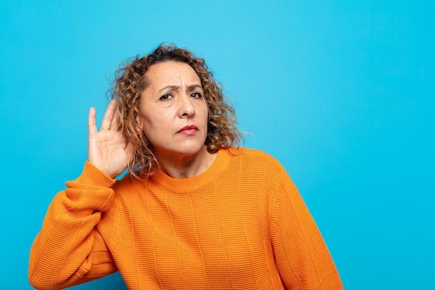 Kobieta w średnim wieku wyglądająca poważnie i zaciekawiona, słuchająca, próbująca usłyszeć tajną rozmowę lub plotkę, podsłuchująca
