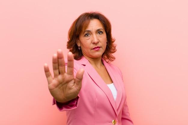 Kobieta w średnim wieku, wyglądająca poważnie, surowo, niezadowolona i wściekła, pokazując otwartą dłoń, robiąc gest stop przeciwko różowej ścianie