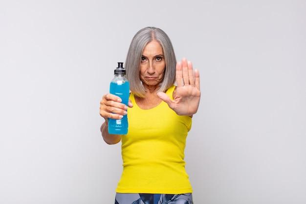 Kobieta w średnim wieku wyglądająca poważnie, surowo, niezadowolona i wściekła pokazuje otwartą dłoń wykonującą gest stopu