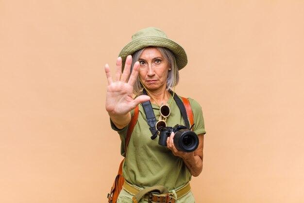 Kobieta w średnim wieku wyglądająca poważnie, surowo, niezadowolona i zła, pokazująca otwartą dłoń wykonującą gest stop