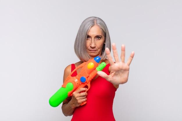 Kobieta w średnim wieku wyglądająca poważnie, surowo, niezadowolona i zła, pokazująca otwartą dłoń wykonującą gest stopu z pistoletu na wodę