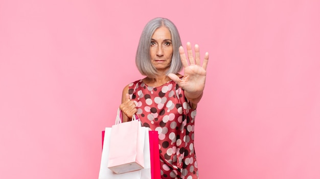 Kobieta w średnim wieku wyglądająca poważnie, surowo, niezadowolona i zła, pokazująca otwartą dłoń wykonującą gest stopu z torbami na zakupy