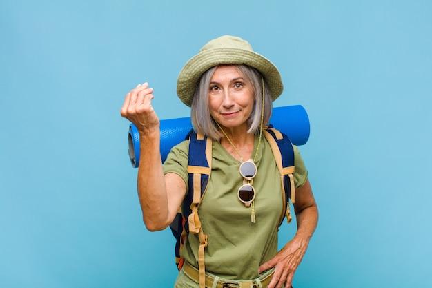 Kobieta w średnim wieku wykonująca kaprysy lub gesty pieniężne, nakazująca spłatę długów!