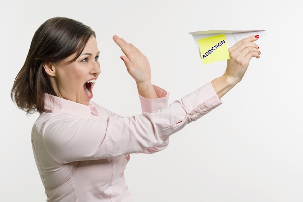 Kobieta w średnim wieku wypuszcza papierowy samolot z słowem uzależnienie.