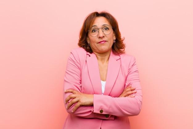 Kobieta w średnim wieku wzrusza ramionami, czuje się zmieszana i niepewna, wątpi ze skrzyżowanymi rękami i zdziwionym spojrzeniem na różowej ścianie