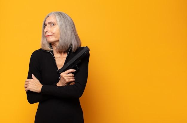 Kobieta w średnim wieku wzruszająca ramionami, zdezorientowana i niepewna, wątpiąca z założonymi rękami i zdziwionym spojrzeniem
