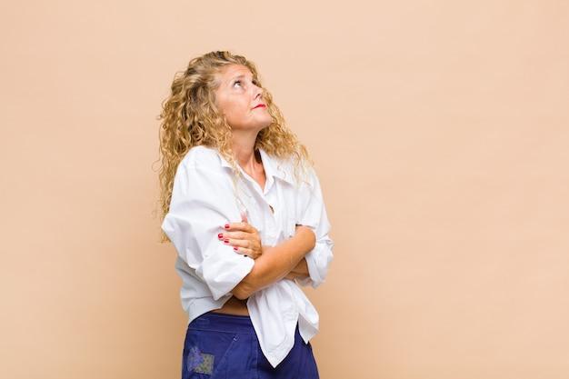 Kobieta w średnim wieku wzruszająca ramionami, zdezorientowana i niepewna, wątpiąca ze skrzyżowanymi rękami i zdziwionym spojrzeniem