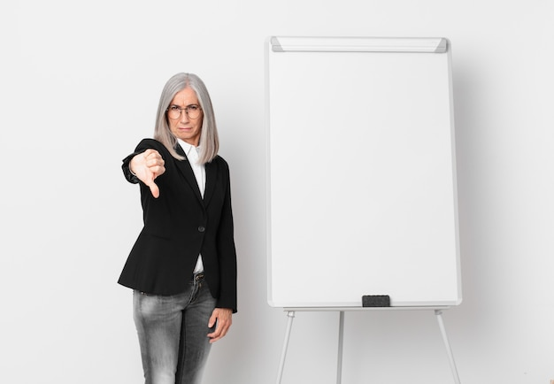 Kobieta w średnim wieku z białymi włosami czuje krzyż, pokazując kciuk w dół i miejsce na kopię na pokładzie. pomysł na biznes
