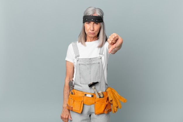 Kobieta w średnim wieku z białymi włosami czuje krzyż, pokazując kciuk w dół i nosząc odzież roboczą i narzędzia. koncepcja sprzątania