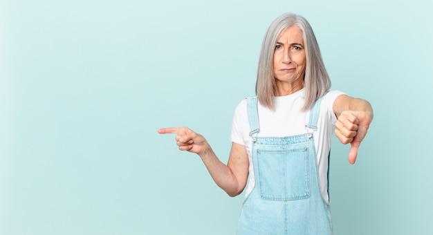 Kobieta w średnim wieku z białymi włosami czuje się krzyżowana, pokazując kciuk w dół i wskazując na bok