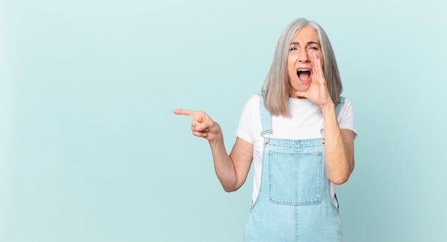 Kobieta w średnim wieku z białymi włosami czuje się szczęśliwa, dając wielki okrzyk z rękami przy ustach i wskazując na bok