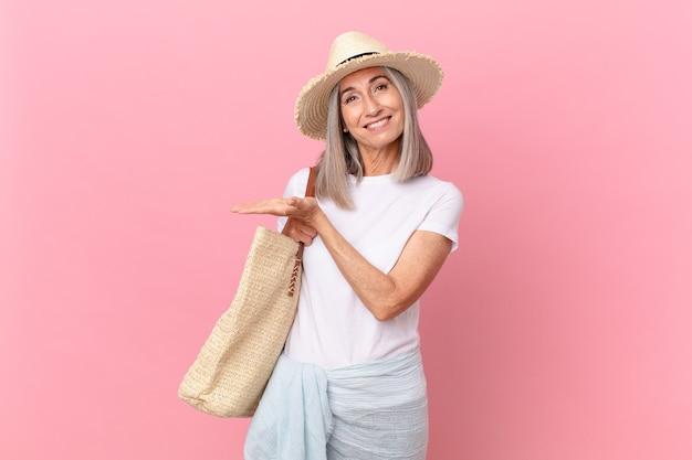 Kobieta w średnim wieku z białymi włosami uśmiecha się radośnie, czuje się szczęśliwa i pokazuje koncepcję. koncepcja lato