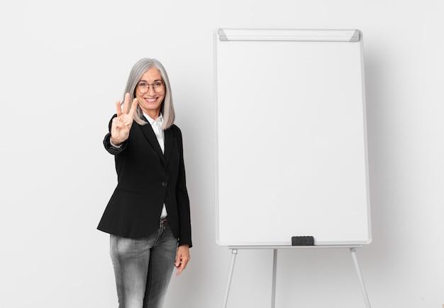 Kobieta w średnim wieku z białymi włosami uśmiechnięta i wyglądająca przyjaźnie, pokazując numer trzy i miejsce na kopię na pokładzie. pomysł na biznes