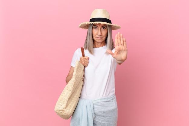 Kobieta w średnim wieku z białymi włosami wygląda poważnie pokazując otwartą dłoń, co robi gest zatrzymania. koncepcja lato