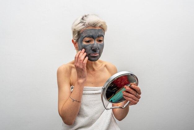 Kobieta w średnim wieku z glinianą maską patrząc w lustro, siedząc na łóżku podczas rutynowej pielęgnacji skóry w domu