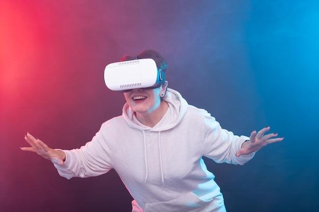 Kobieta w średnim wieku z goglami wirtualnej rzeczywistości. studio shot, czerwono-niebieska powierzchnia.