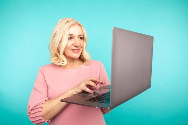 Kobieta w średnim wieku z laptopem na białym tle sprawdzić pocztę i pisać na maszynie.